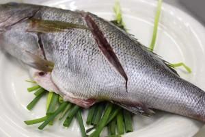 皿の上にネギをしき、その上に魚を載せます。